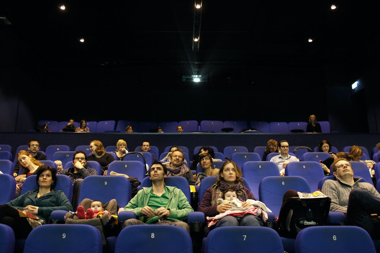 Ouders kijken met hun baby naar de film I give it a year in bioscoop Pathe in Breda. Tijdens speciale filmvertoningen voor ouders met baby's blijft het licht aan, staat het geluid zacht en kunnen ouders heen en weer lopen om de baby te verschonen.