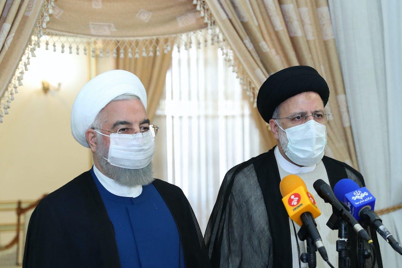 Vertrekkende president Hassan Rouhani (links) naast Ebrahim Raisi tijdens een persconferentie.