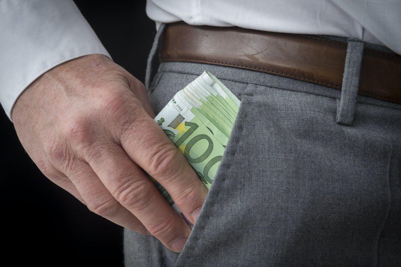Een zakenman met een stapel van honderd eurobiljetten