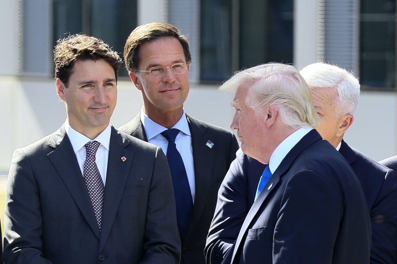 De Amerikaanse president Donald Trump (R) loopt voorbij aan onder meer minister-president Mark Rutte (M) en de Canadese president Justin Trudeau (L) tijdens de officiële opening van een NAVO-bijeenkomst in Brussel.