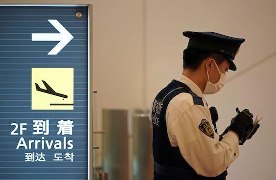 Agent met mondkapje op de internationale luchthaven van Tokio