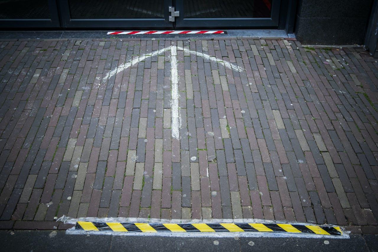 Strepen die aangeven dat klanten 1,5 meter afstand moeten bewaren in een winkelstraat in Haarlem.
