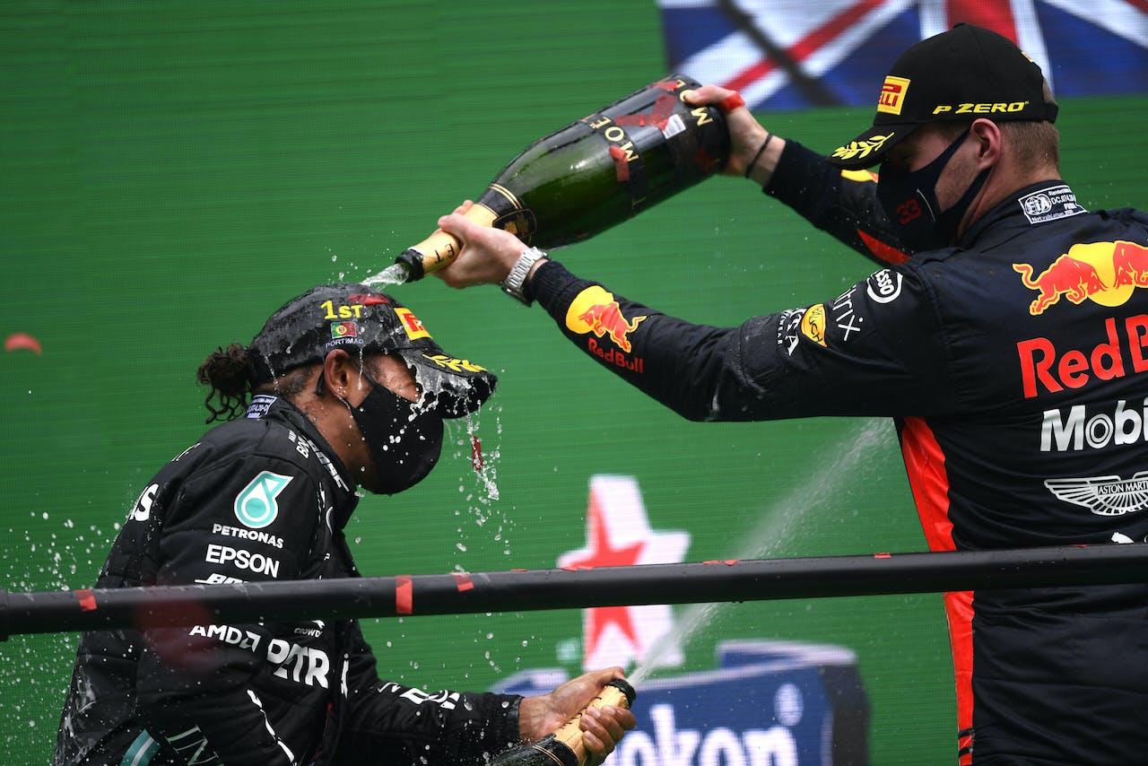 Formule 1-coueurs Lewis Hamilton en Max Verstappen spuiten champagne op het podium na een race.
