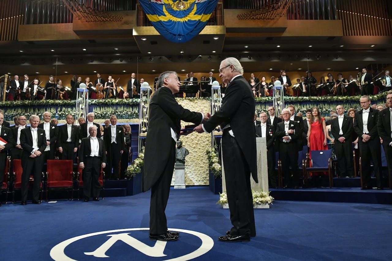 De vorige winnaar, de Britse auteur Kazuo Ishiguro, krijgt de Nobelprijs van koning Carl XVI Gustaf van Zweden tijdens de ceremonie in het Concertgebouw in Stockholm.