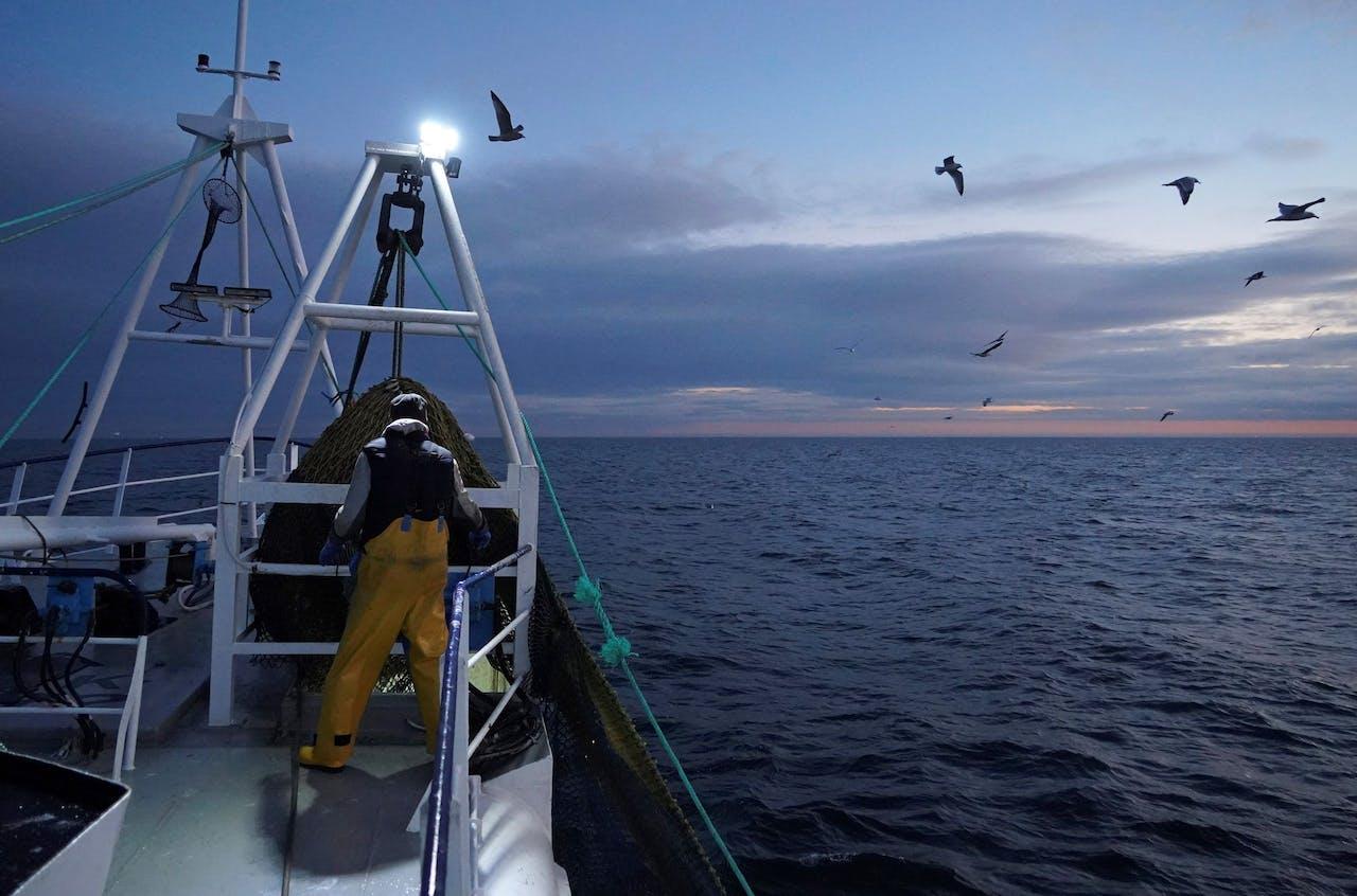 Een visser aan boord van een Brits vissersschip