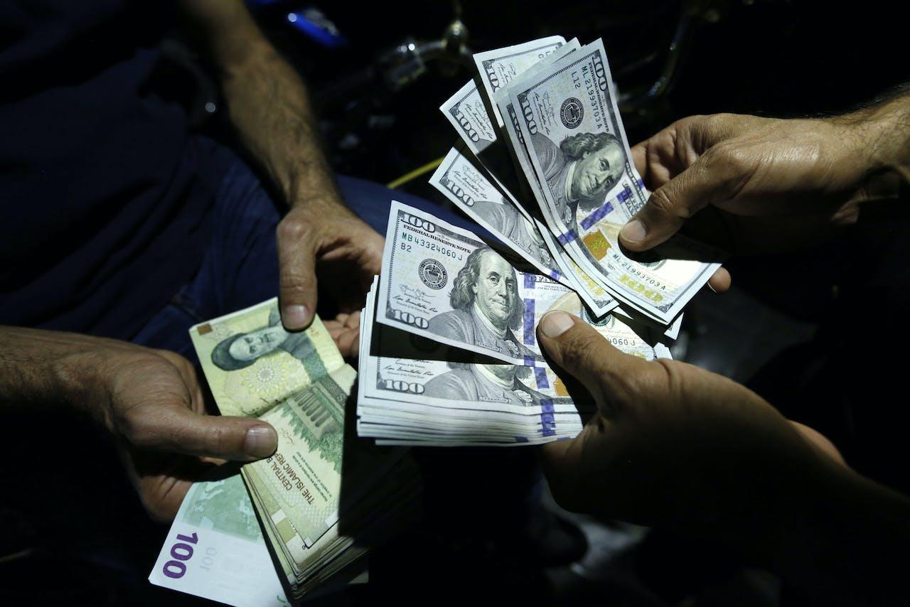 Iraans rial's en Amerikaanse dollars worden gewisseld in Teheran.
