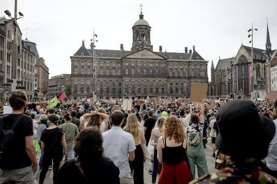 Demonstranten tijdens het protest op de Dam van maandag hielden zich niet aan de anderhalvemeter-regel