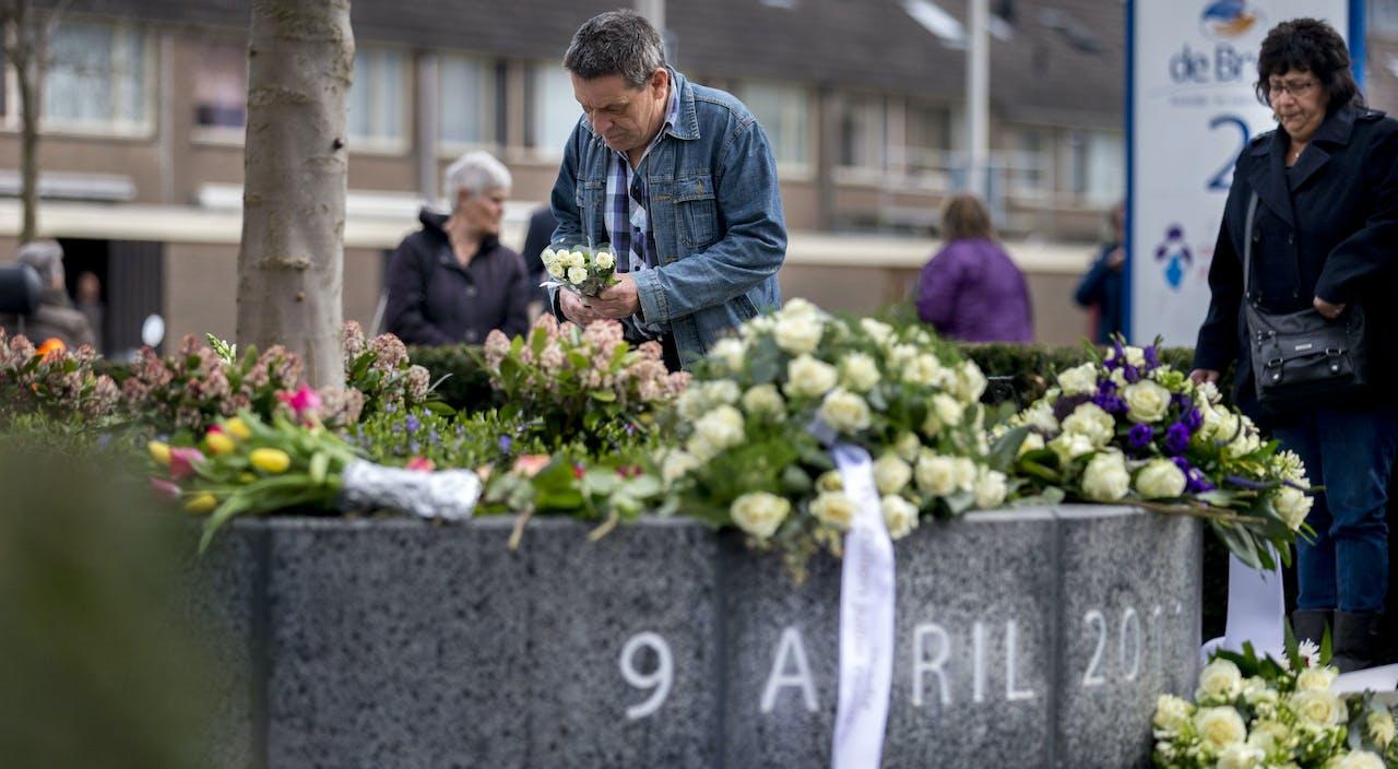 Mensen leggen bloemen bij het monument ter nagedachtenis aan de slachtoffers van het schietdrama in winkelcentrum de Ridderhof.