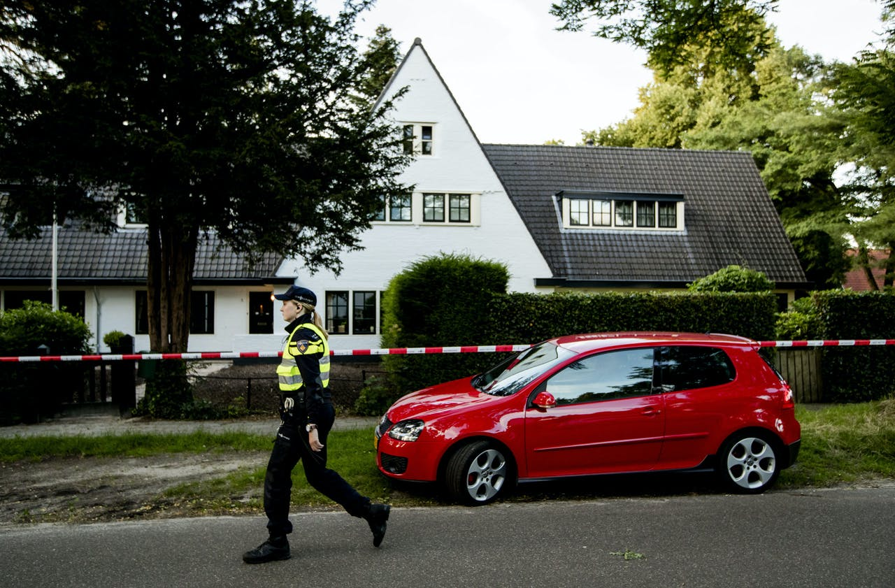 Een agent bij het huis van Koen Everink voorafgaand aan de reconstructie van de moord op de zakenman.