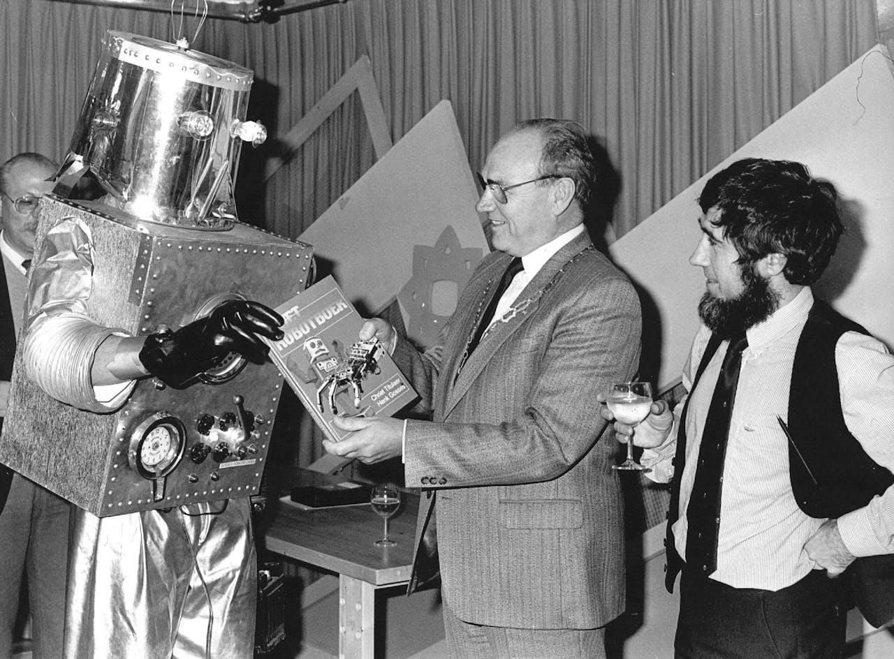 November 1986: een 'robot' overhandigt het eerste exemplaar van het Robotboek aan de burgemeester van Houten. Rechts een van de auteurs, Chriet Titulaer.