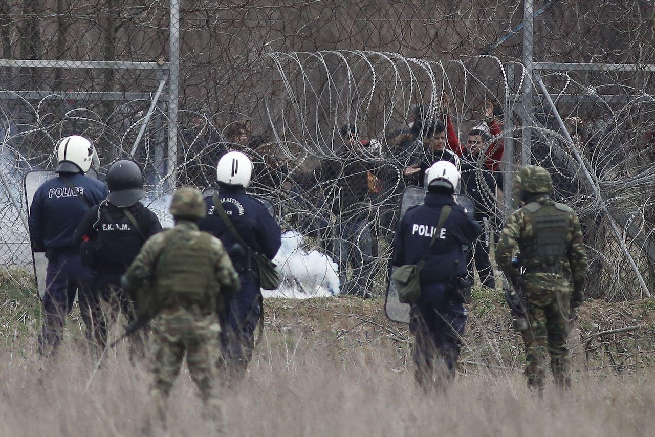 Griekse oproerpolitie en militairen proberen migranten tegen te houden, die de Turks-Griekse grens willen oversteken.