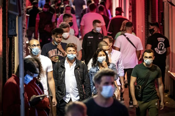 Toeristen met mondkapjes op de Wallen in Amsterdam