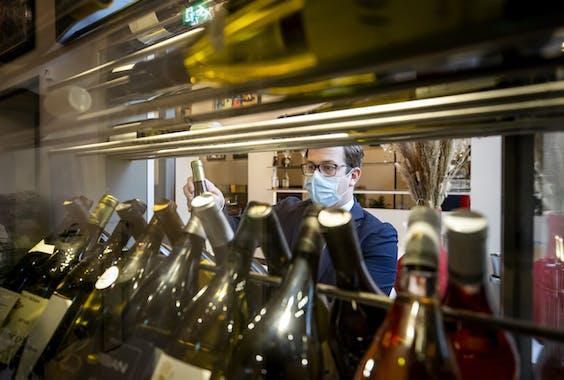 Een ober bij de wijnkast van Brasserie Ambassade,