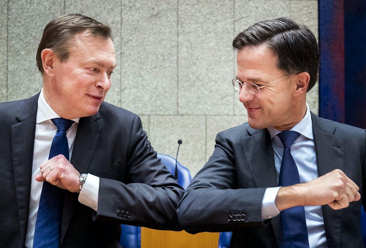 Premier Mark Rutte geeft minister Bruins voor Medische Zorg een ellebooggroet.