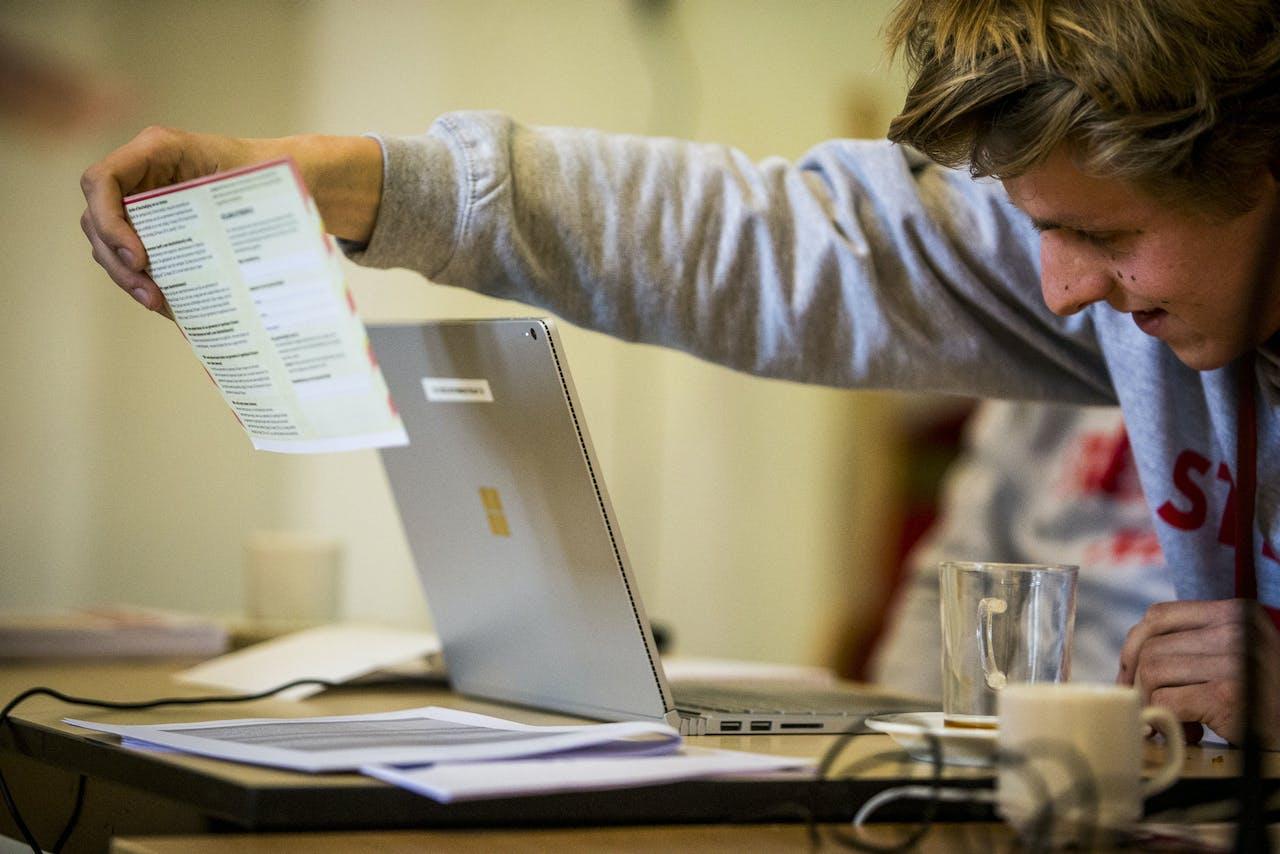 Een medewerker scant een stembiljet. Het stembureau in Groningen doet mee aan het experiment Stemmen Telt!