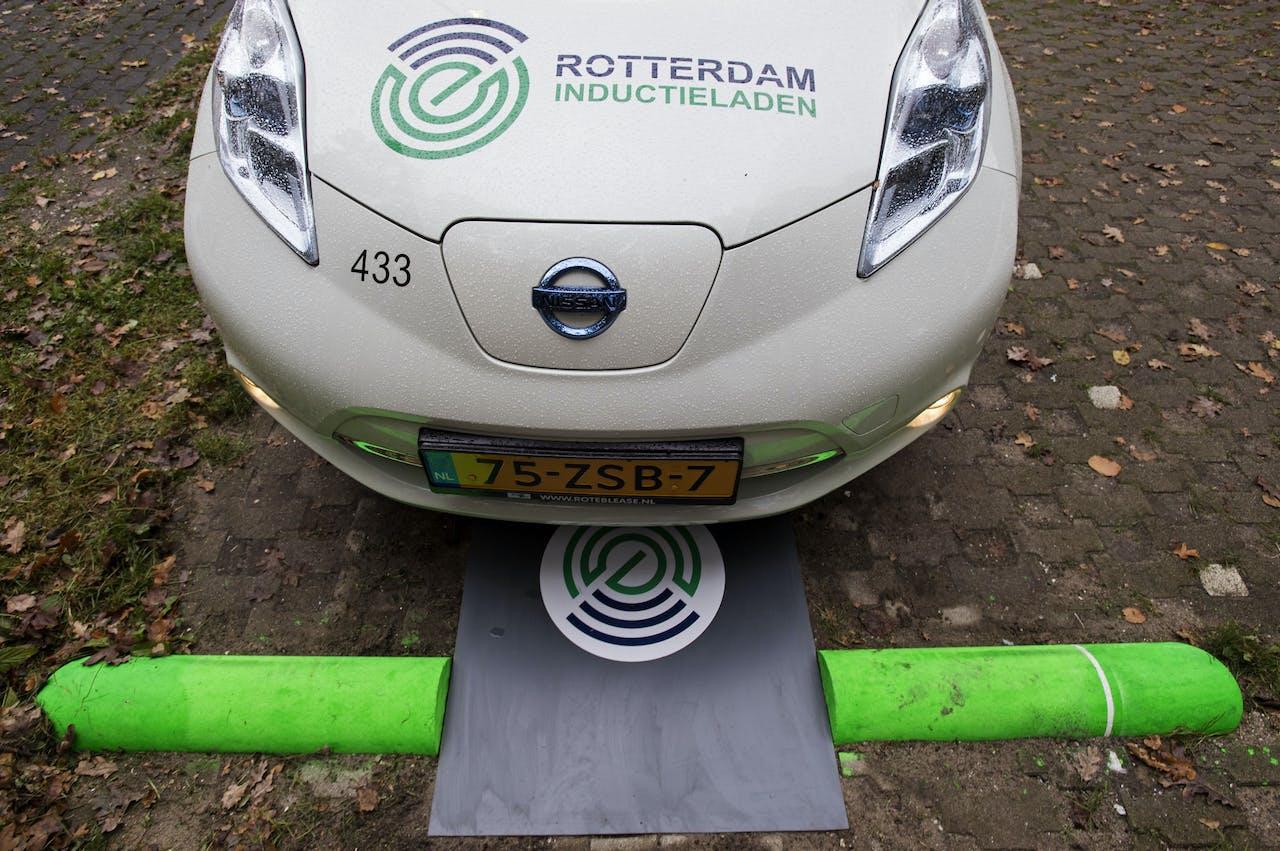 Een elektrische auto wordt opgeladen boven een laadplaat.