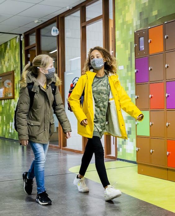 Leerlingen van een middelbare school dragen mondkapjes in de gang. Het dragen van mondkapjes is op veel scholen verplicht, sinds de nieuwe stijging van het aantal coronabesmettingen.
