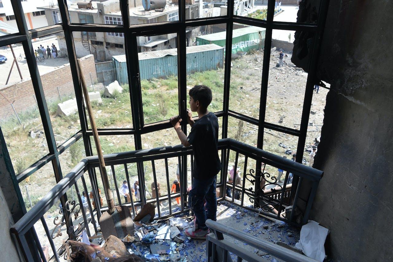 Kabul - Een dag na een aanslag op het politiebureau kijkt een jongen uit het raam.