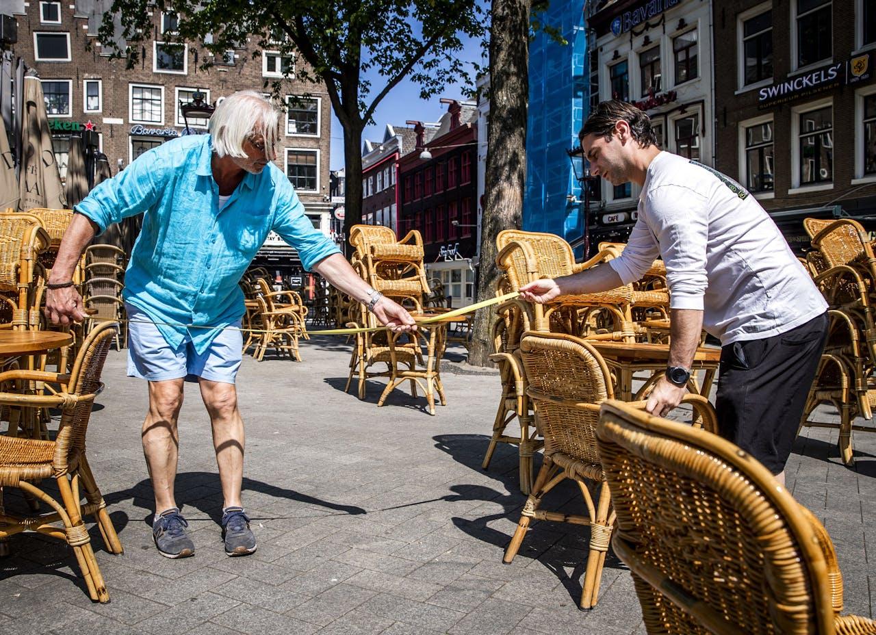 2020-05-21 12:05:45 AMSTERDAM - Een kroegbaas meet de afstand tussen tafels op een terras voorafgaand aan de heropening van de terrassen op 1 juni. Het is zomers weer op Hemelvaartsdag, en ondanks dat de horeca nog dicht is vanwege de coronamaatregelen gaan veel mensen naar buiten. ANP REMKO DE WAAL