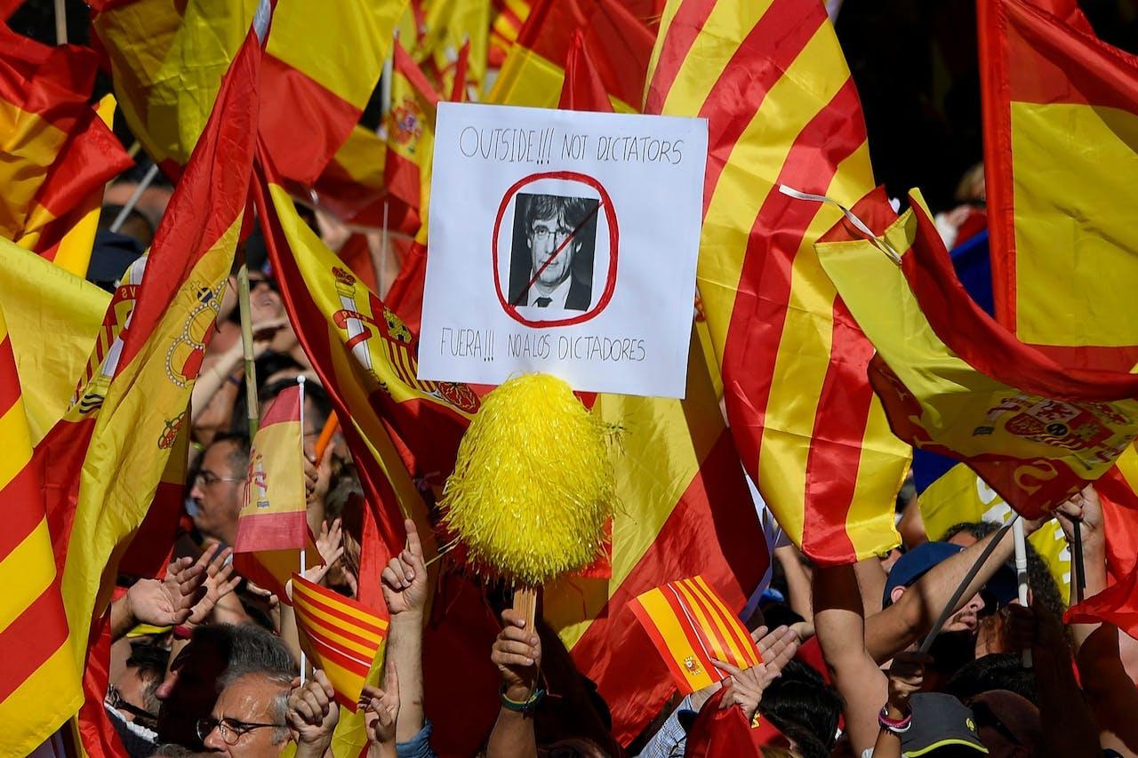 Tijdens een demonstratie van voorstanders van Spaanse eenheid, gisteren in Barcelona, houdt een betoger een bord omhoog met het portret van Puigdemont en de tekst: 'weg met de dictators'.