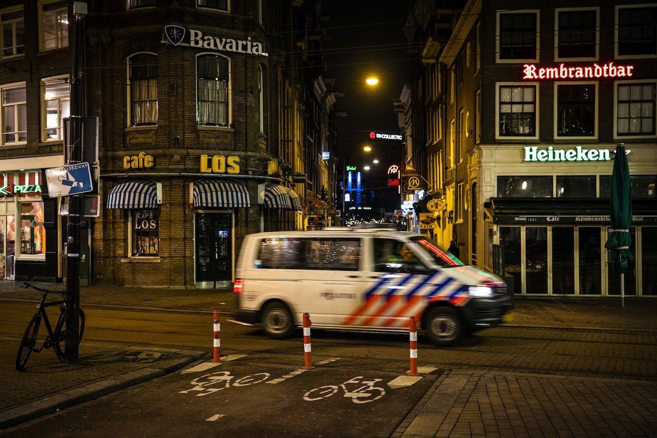 Een politieauto op het Rembrandtplein in het centrum van Amsterdam. De invoering van een avondklok ligt voor het kabinet als serieuze optie op tafel.