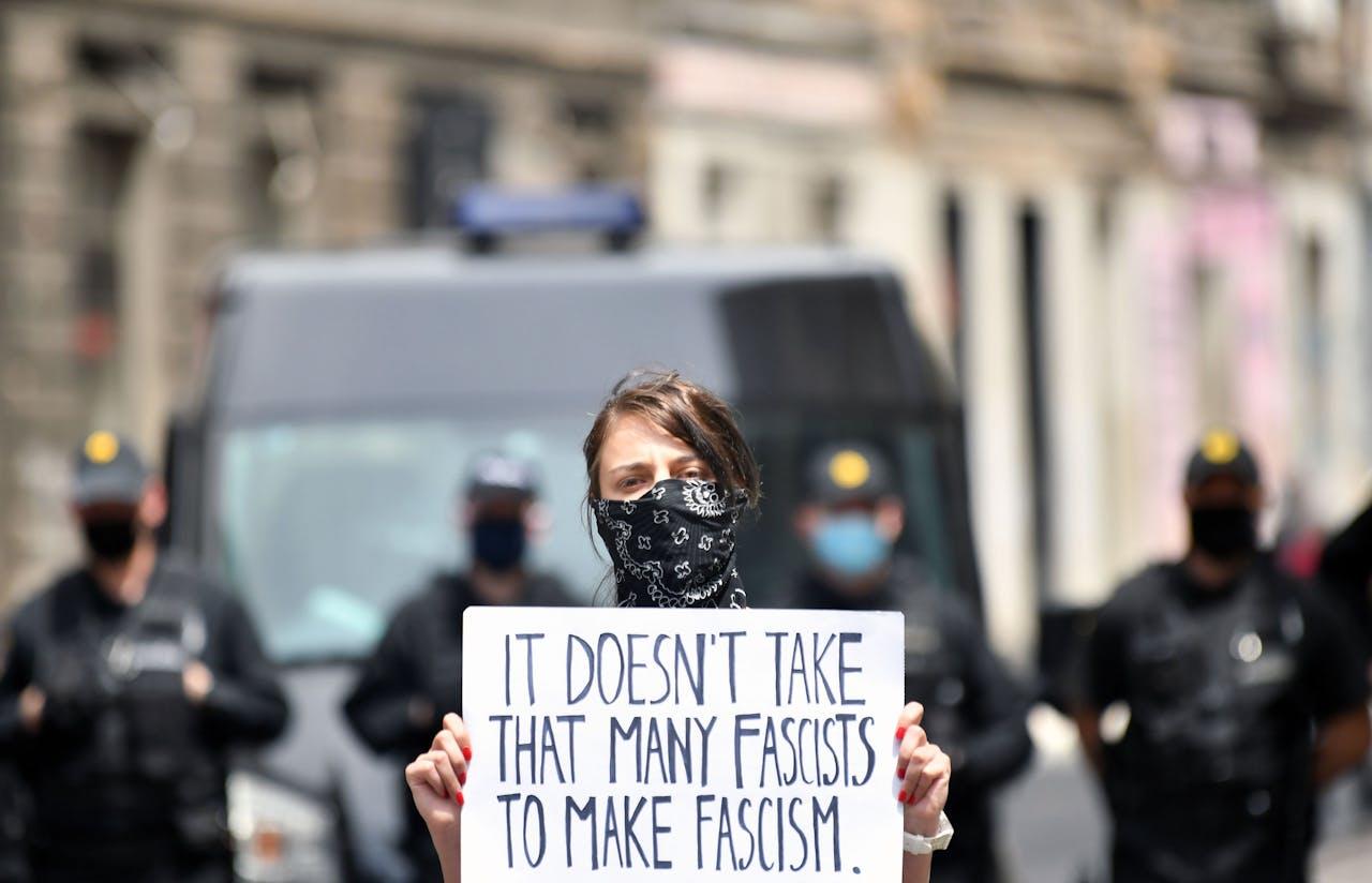 Een vrouw houdt een protestbord omhoog. Zij is het niet eens met de herdenking van de slachtoffers van Bleiburg in Sarajevo.