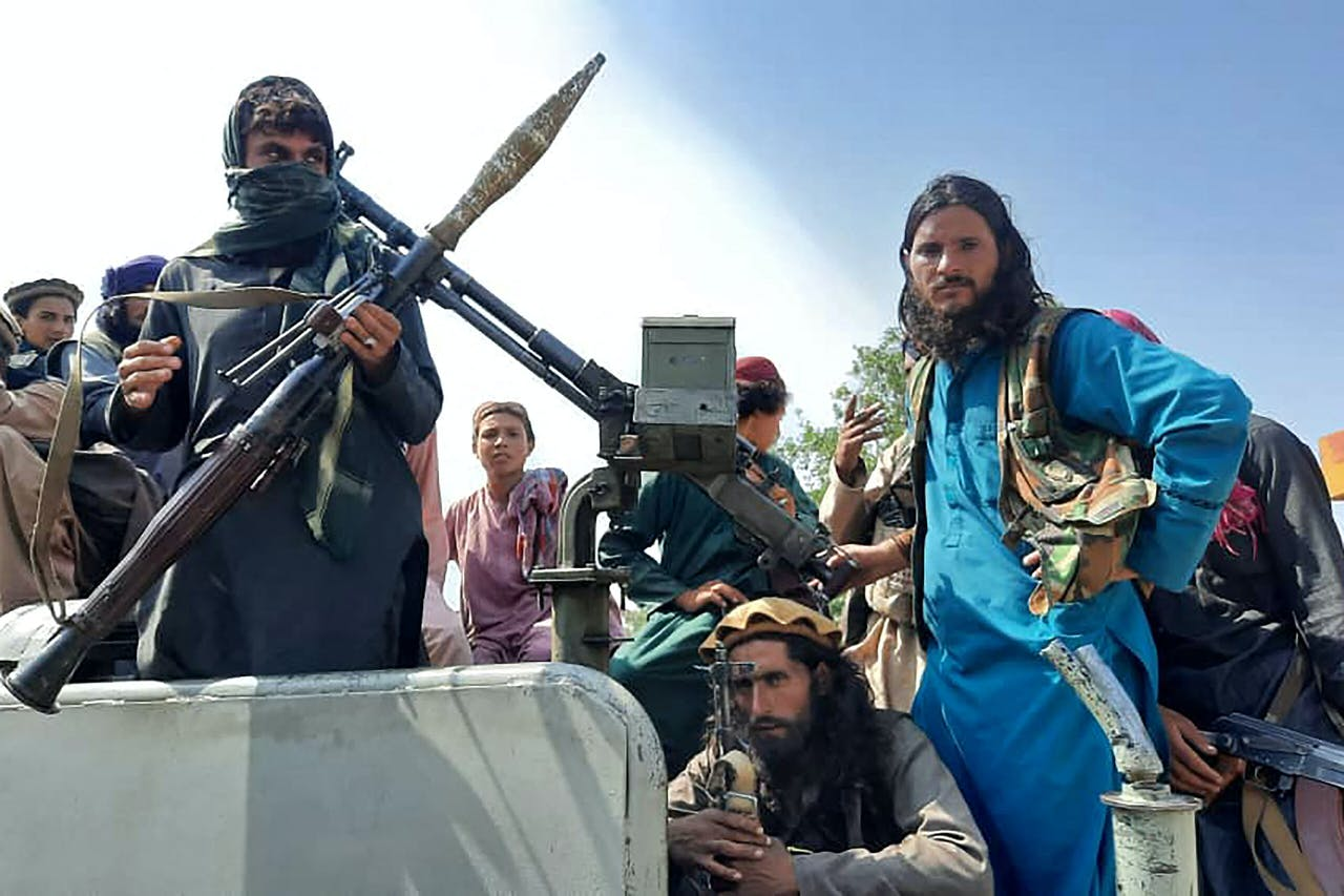 Taliban fighters sit over a vehicle on a street in Laghman province on August 15, 2021. AFP
