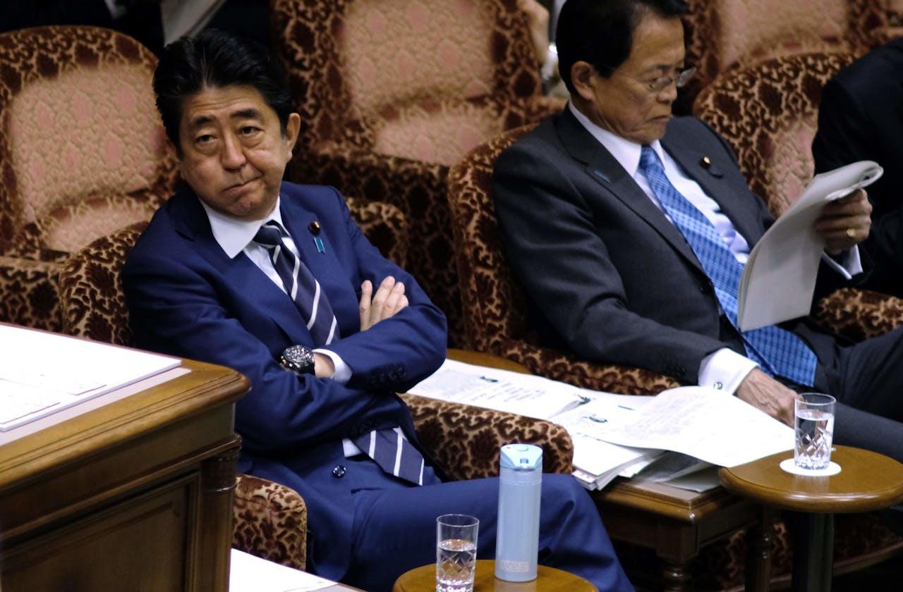 Premier Shinzo Abe (L) and minister Taro Aso.