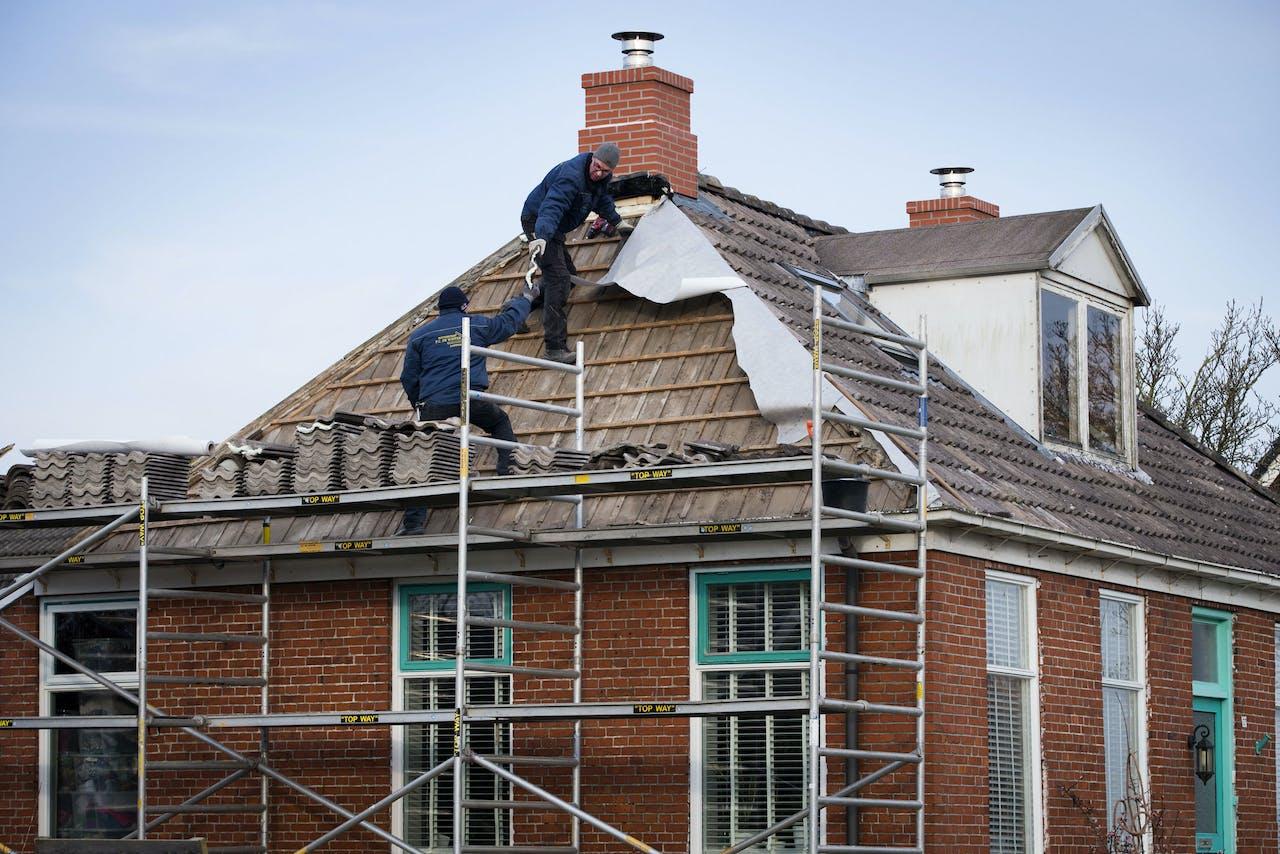 Bouwvakkers herstellen aardbevingsschade aan een schoorsteen van een huis in het Groningse dorp 't Zandt.