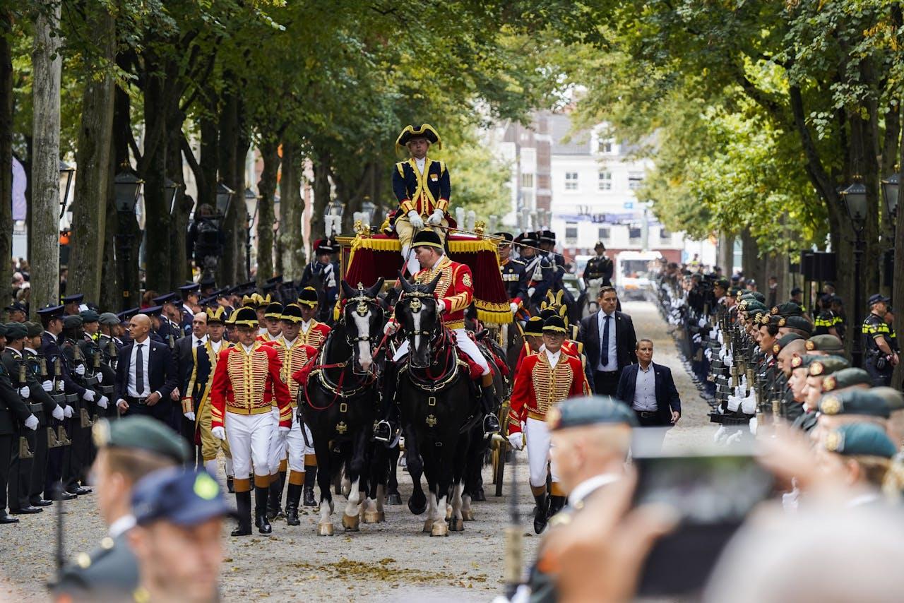 Publiek kijkt naar de Glazen Koets onderweg van paleis Noordeinde naar de Ridderzaal op Prinsjesdag.