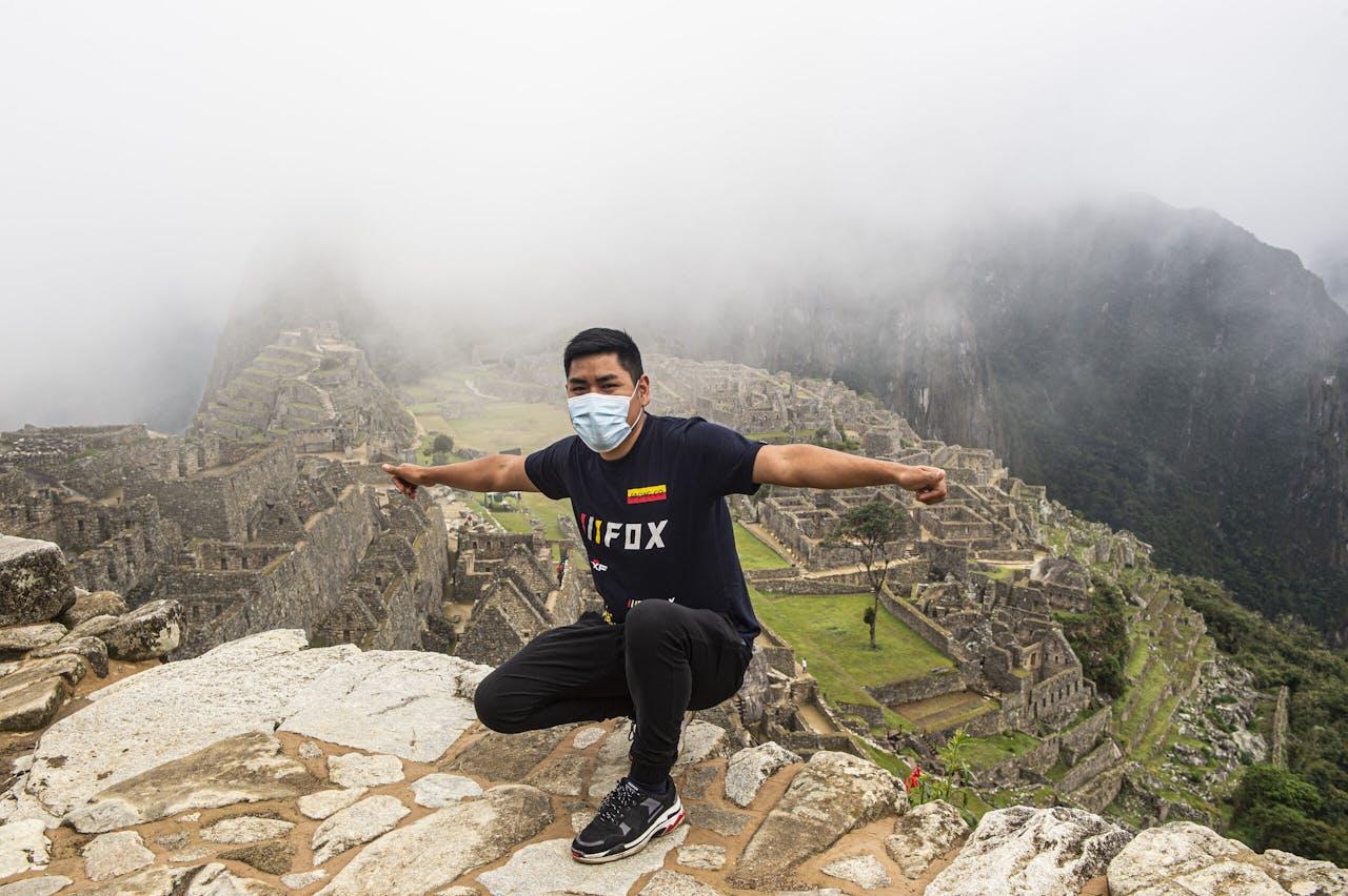 Een toerist poseert bij Machu Picchu. Dit Peruaanse wereldwonder ging van medio maart tot en met oktober op slot. Per dag zijn er nu 675 toeristen welkom; dat waren er voorheen ruim tweeduizend. ERNESTO BENAVIDES / AFP
