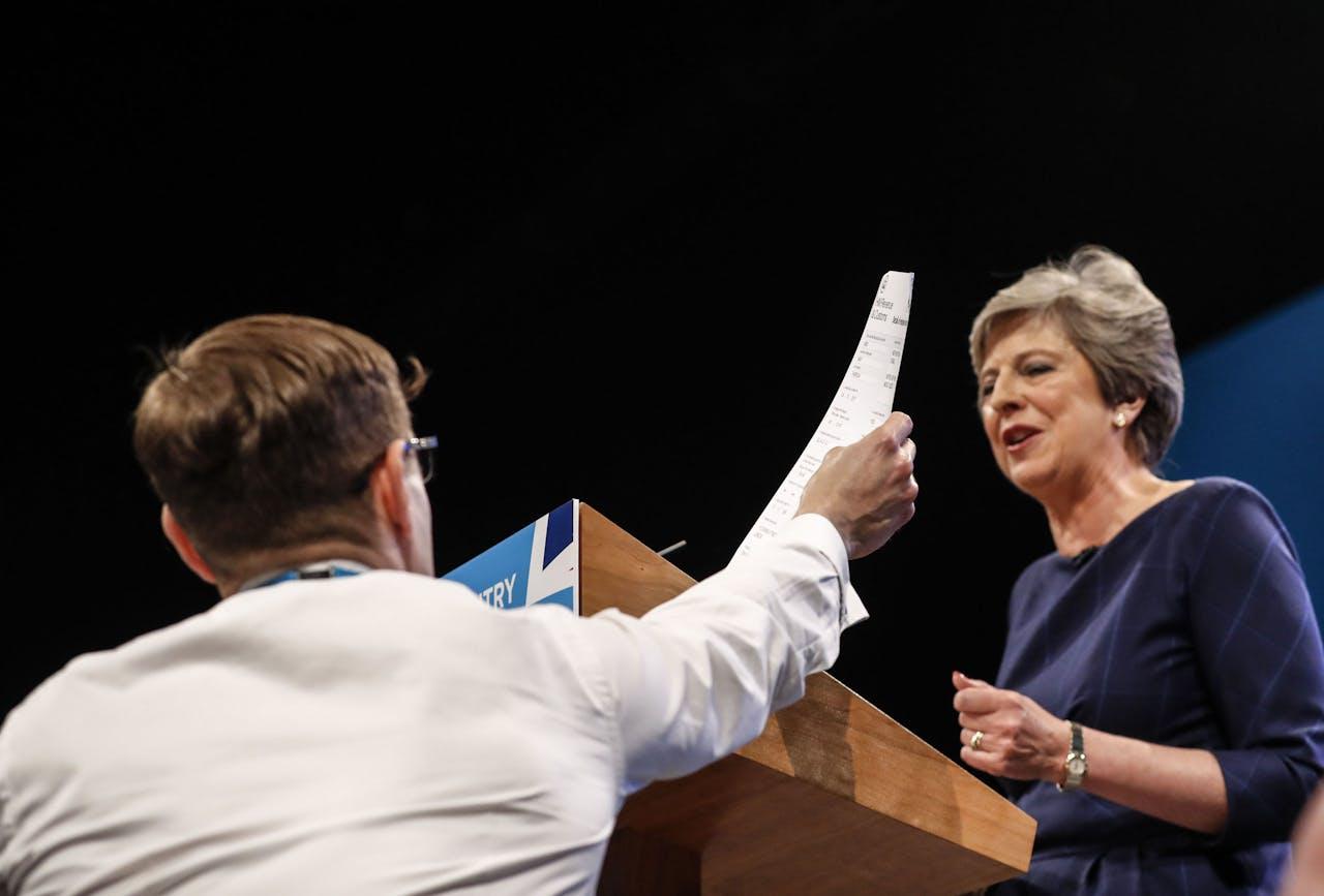 Een komiek overhandigt Theresa May tijdens haar toespraak haar 'ontslagbrief'