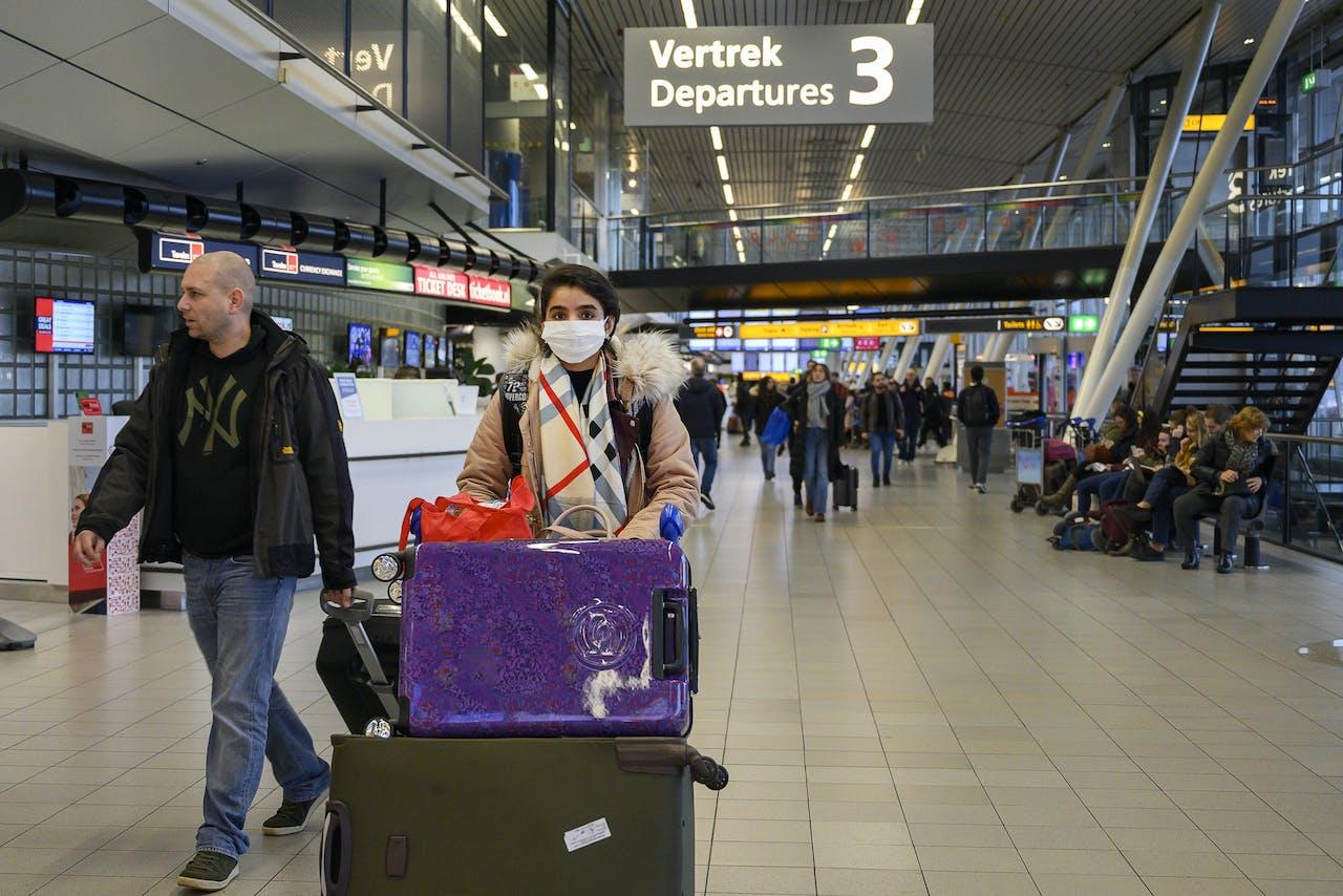 Reizigers op Schiphol dragen een mondkapje.