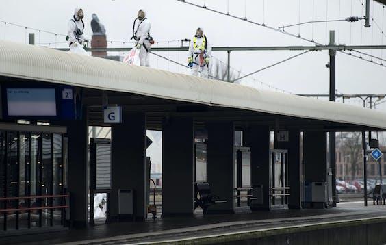 Witte pakken van asbestbestrijders op een stationsdak in Roermond.