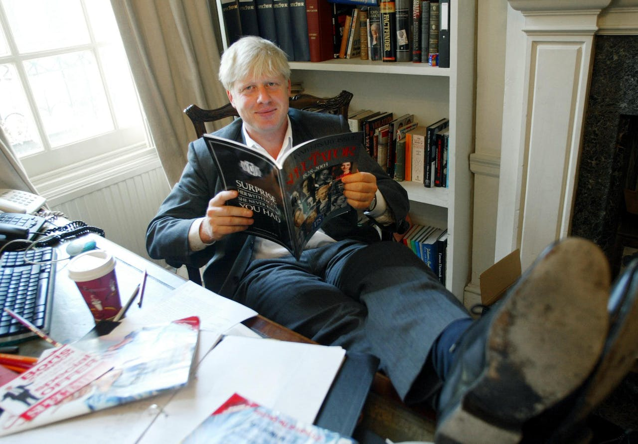 (FILES) In this file photo taken on September 25, 2003 TO GO WITH STORY: LIFESTYLE-BRITAIN-MEDIA. The editor of The Spectator magazine, Boris Johnson, sits in his London office reading the anniversary issue of The Spectator marking 175 years of publication. AFP PHOTO/Jim WATSON - Since coming to power in July, Boris Johnson has shed his image as a jovial, wisecracking mophead to reveal a ruthless streak that has marked him out since childhood. (Photo by Jim WATSON / AFP)
