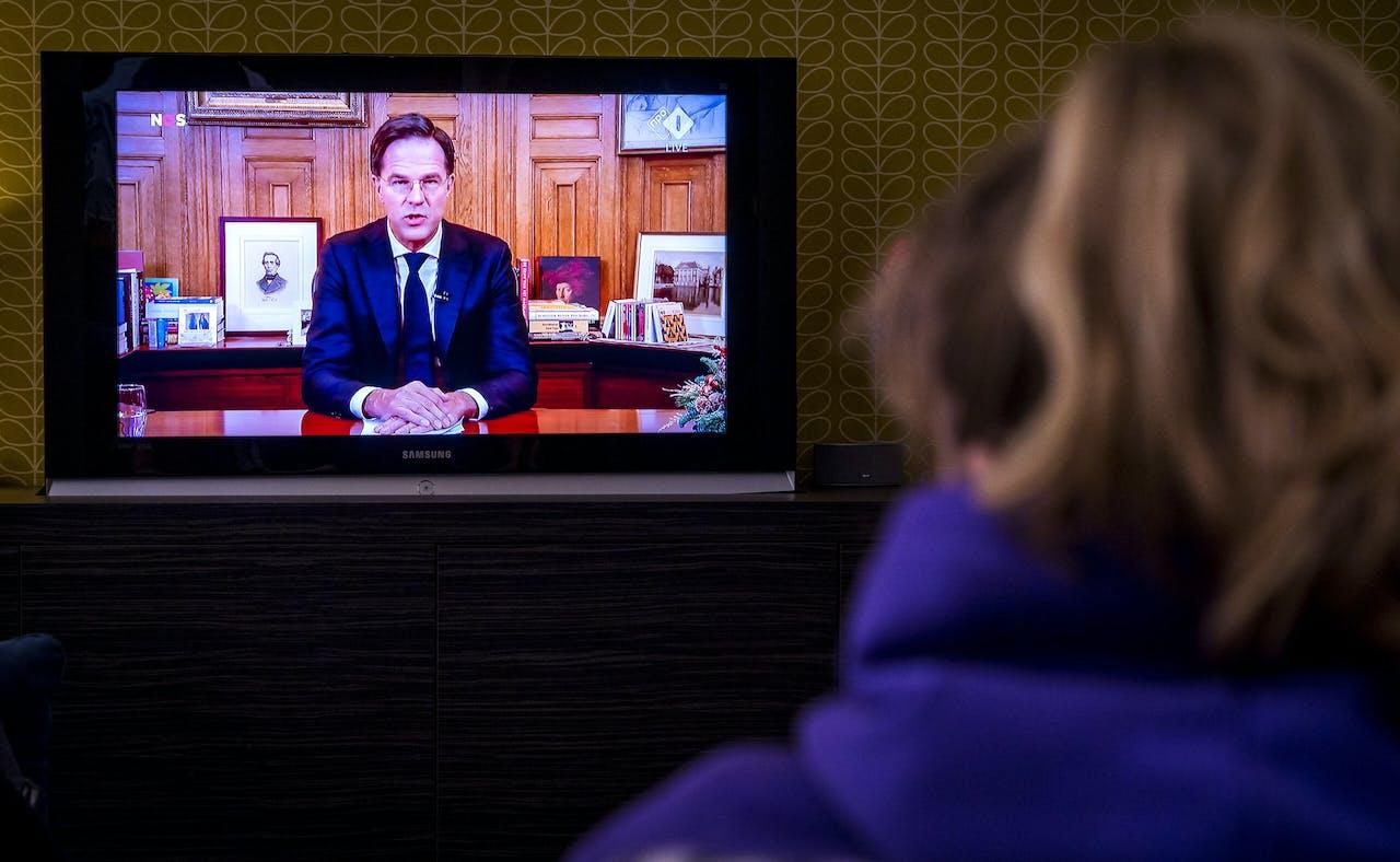 Een gezin met schoolgaande kinderen kijkt naar de toespraak van premier Mark Rutte over verscherping van de coronaregels die op televisie werd uitgezonden. Het was de tweede keer dit jaar dat de minister-president een toespraak over de coronacrisis hield vanuit het Torentje.