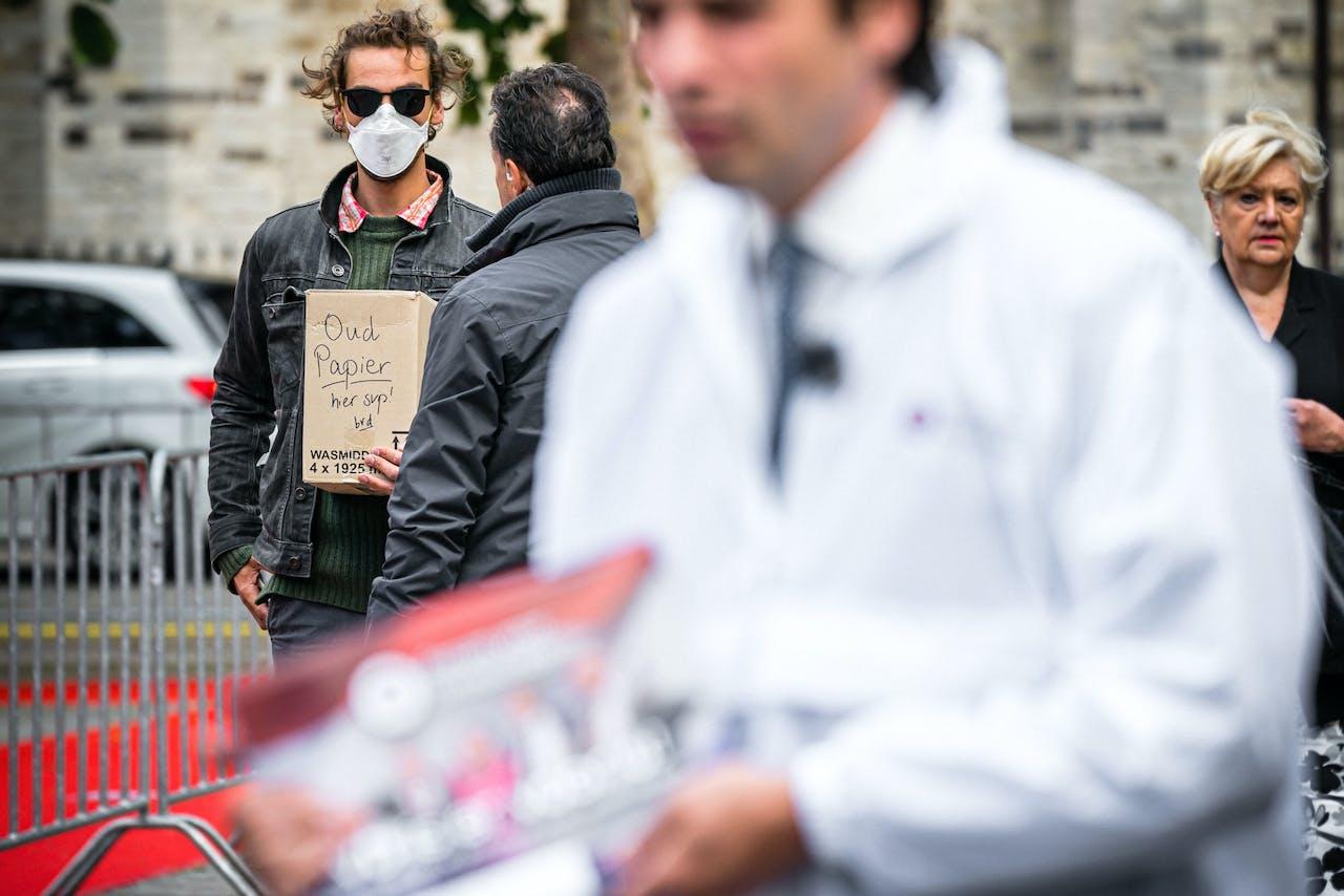 Thierry Baudet van de partij Forum voor Democratie deelt een FVD krant uit aan voorbijgangers. Op de achtergrond is Jasper van den Elshout zichtbaar met zijn éénmansprotest.