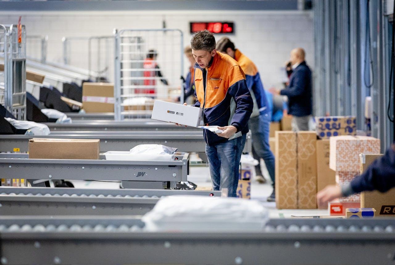 Medewerkers sorteren pakketten in het nieuwe pakketsorteercentrum van PostNL. Het nieuwe centrum moet de drukte rond de feestdagen beter opvangen.