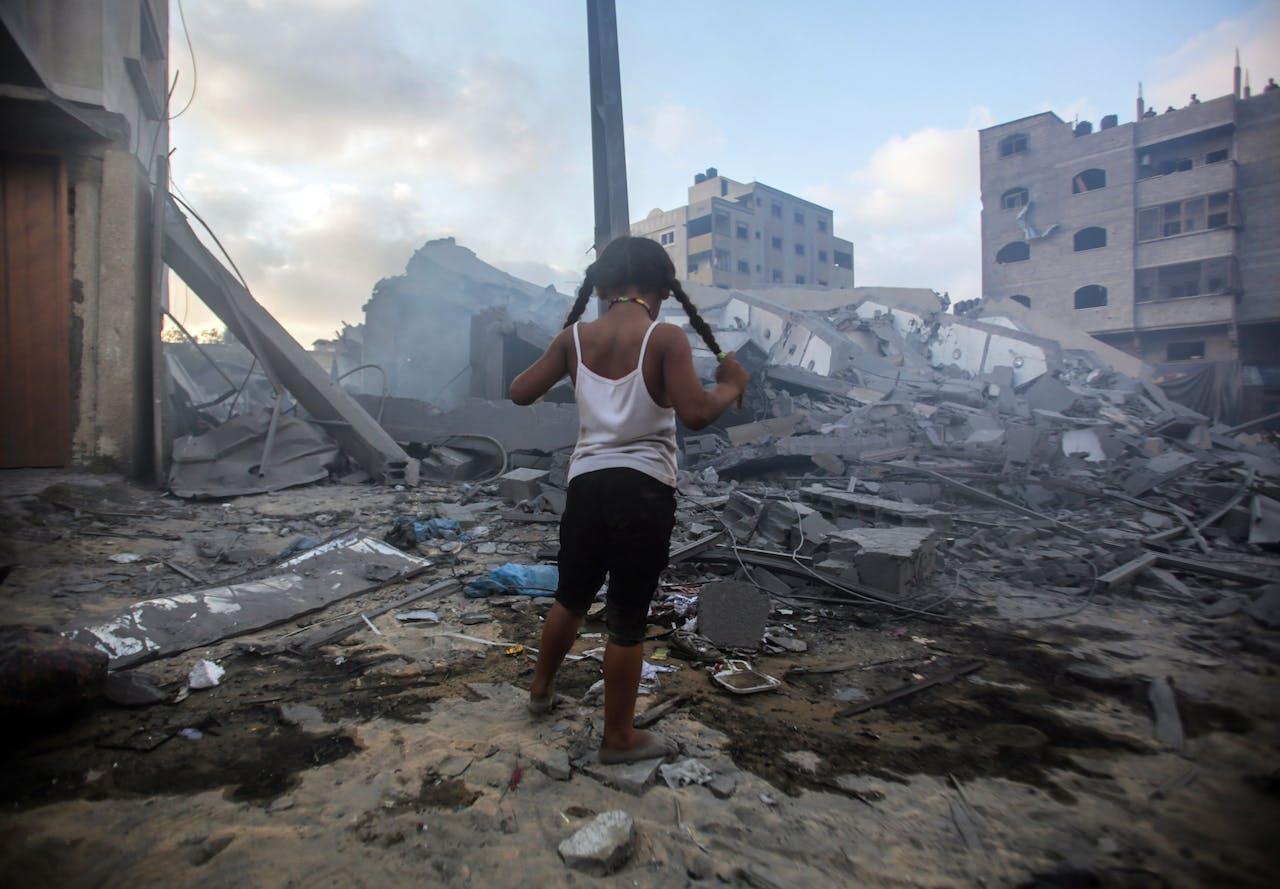 Een kind kijkt naar de ravage die is aangericht door een Israelisch luchtbombardement