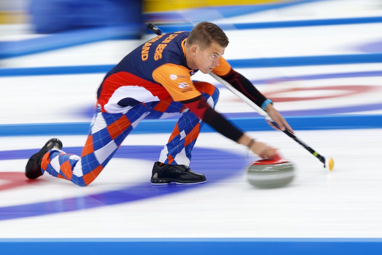 Danny van den Berg van het Nederlandse team doet aan curling in een kekke broek.