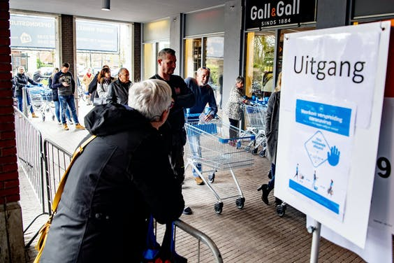 Medewerkers Albert Heijn werken achter plastic