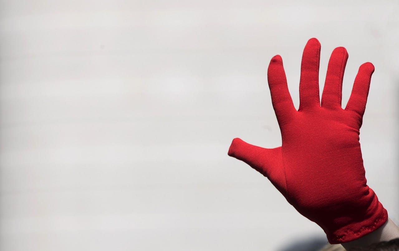 Een demonstrant draagt een rode handschoen, een symbool tegen seksueel geweld