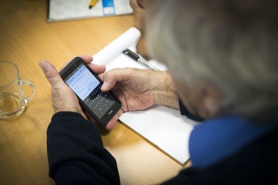 Een oudere in de weer met een smartphone.