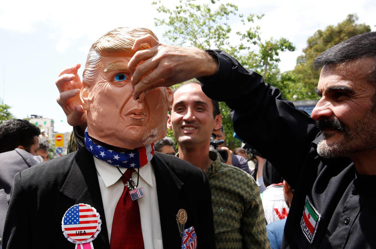 Demonstrators stand around an Iranian man that wears a mask of the US President Donald J. Trump during an anti-US rally, to show their support of Iran's decision to pull out from some part of nuclear deal, in Tehran.