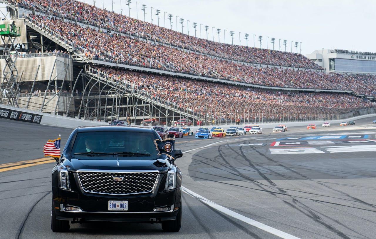 Trump en vrouw Melania rijden onder luid gejuich een rondje over de NASCAR-racebaan in de presidentiële limo.