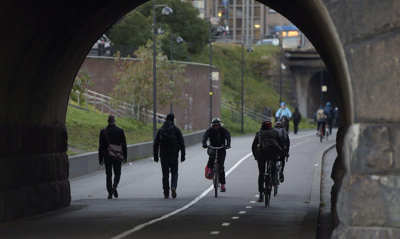 Fietsers en voetgangers op de Baana-weg, die gebouwd is in een oude spoorweg in een ravijn en naar het centrum van Helsinki leidt.