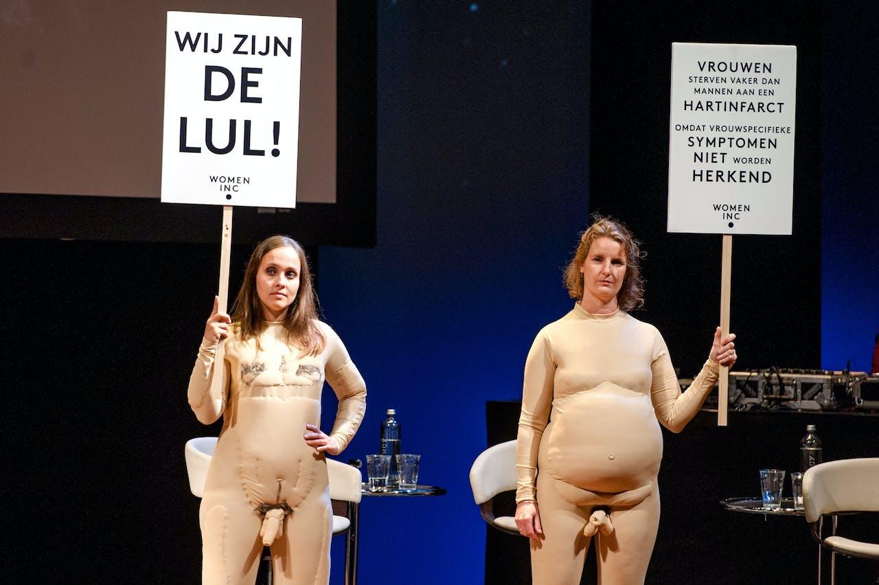 Twee vrouwen staan in naaktpakken op het podium van vrouwennetwerk WOMEN Inc.,