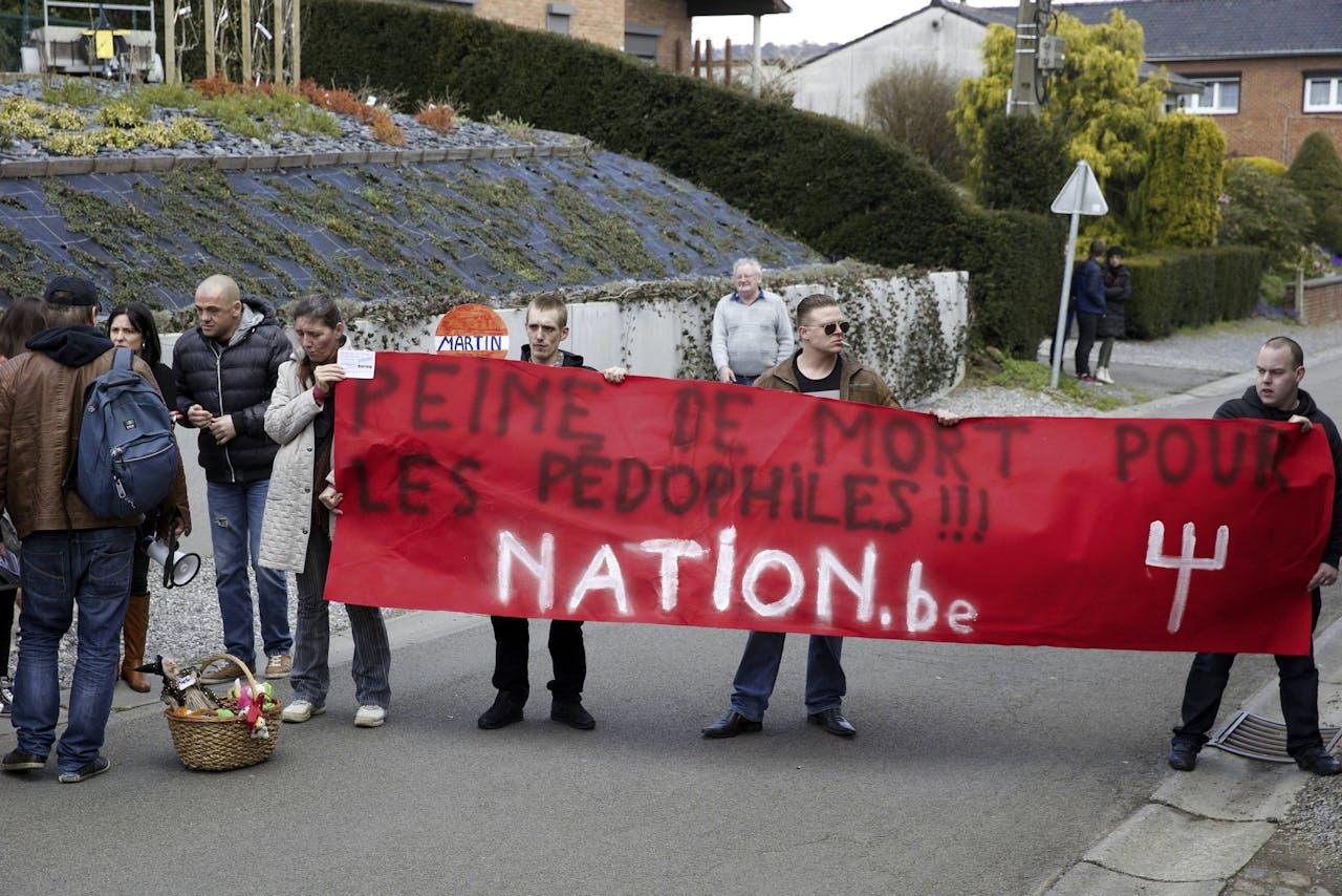 """Demonstranten in 2015 met het spandoek """"doodstraf voor pedofielen"""" voor het huis van voormalig rechter, die zijn huis verhuurt aan de vrouw van Dutroux."""