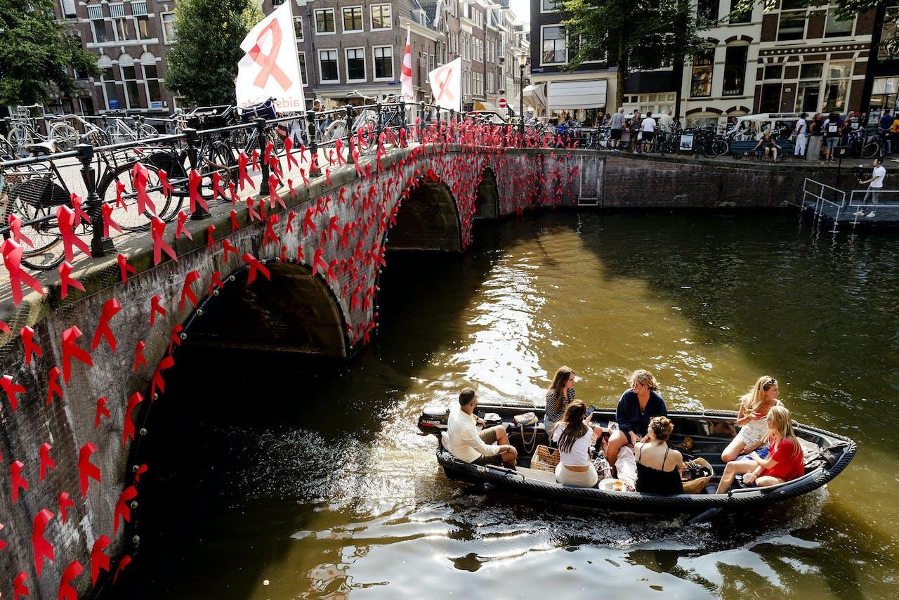 Met rode Ribbons versierde brug onderweg van de fakkeltocht Positive Flame door de binnenstad om aandacht te vragen voor mensen met hiv. De fakkeldragers zijn mannen en vrouwen die leven met hiv in Nederland. De fakkeltocht vond plaats in de week van de internationale aidsconferentie AIDS2018.