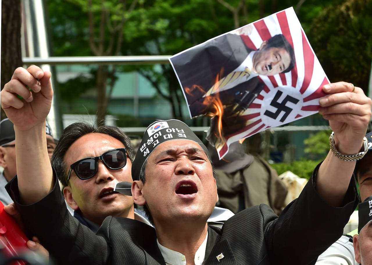 A South Korean activist burns a poster showing a picture of Japan's Prime Minister Shinzo Abe depicted as former German chancellor Adolf Hitler.